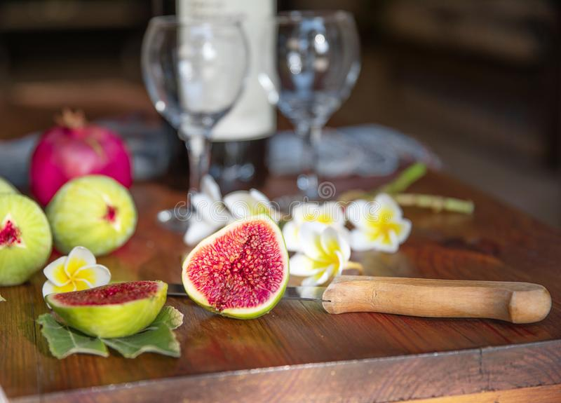 Fresh whole and cut fruits figs, pomegranate and exotic plumeria flowers on wooden table with bottle of wine and glasses stock photos