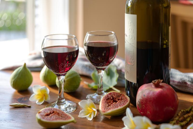 Fresh whole and cut fruits figs, pomegranate and exotic plumeria flowers on wooden table with bottle of wine and glasses. On window background. Still life stock photos
