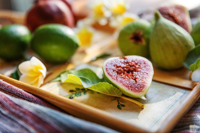 Fresh whole and cut fruits figs, pomegranate and exotic plumeria flowers on wooden tray. Natural background. Still life.  stock photography
