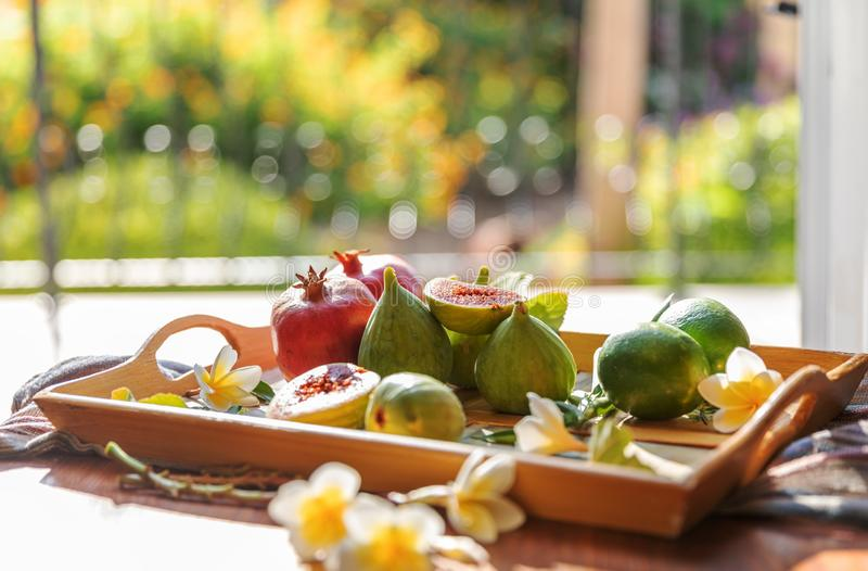 Fresh whole and cut fruits figs, pomegranate and exotic plumeria flowers on wooden tray on table next to open window stock photos