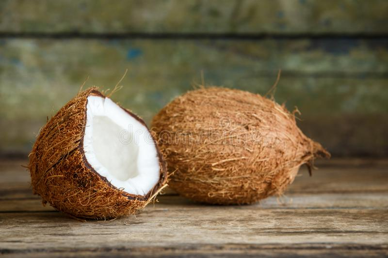 Whole and cut in half coconuts on wood background stock images