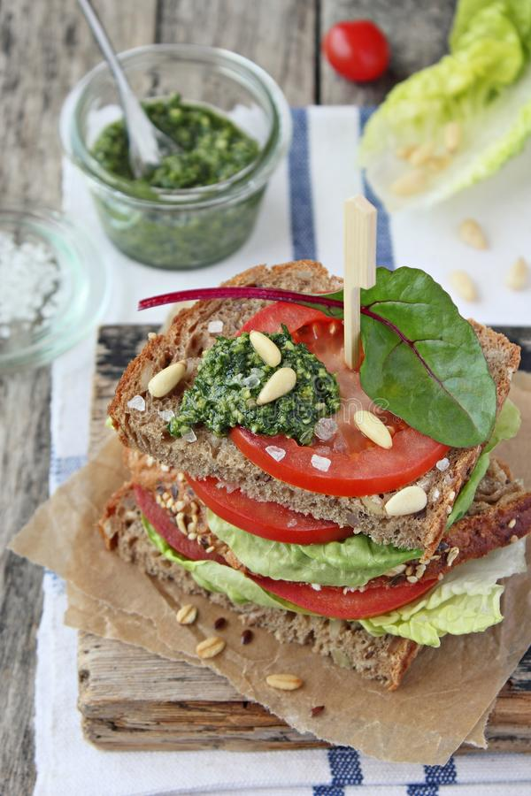 Fresh whole grain bread sandwich with green salad mix,tomato and pesto royalty free stock photo