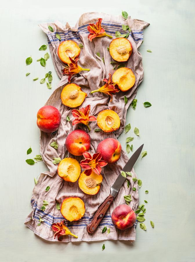 Fresh whole and half peaches composing on kitchen towel with leaves, flowers and knife, top view. Flat lay royalty free stock photos