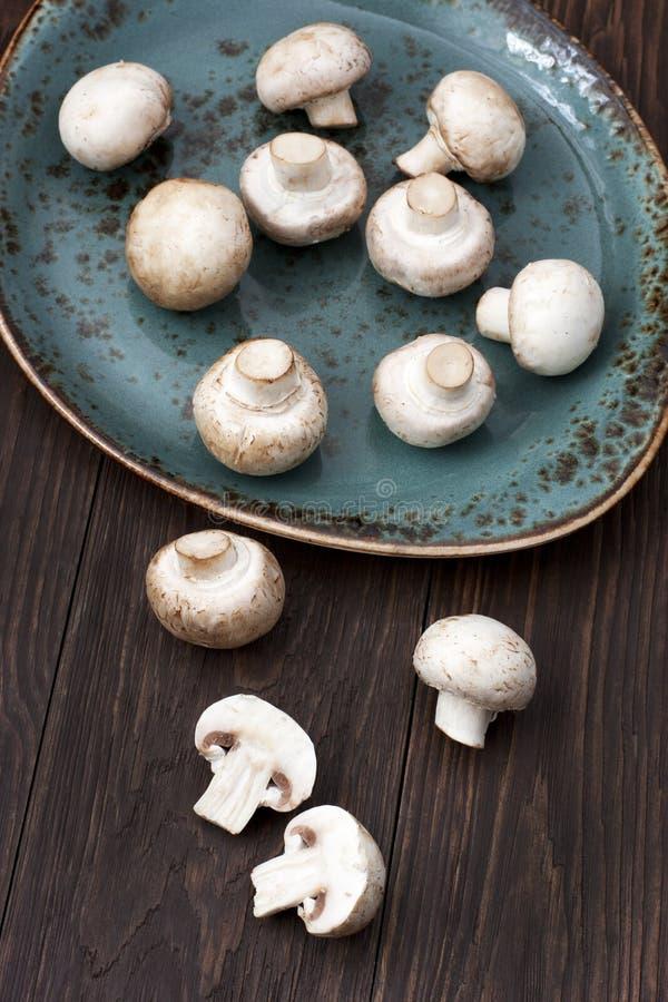 Fresh whole mushrooms. Button mushroom on ceramic plate royalty free stock photography
