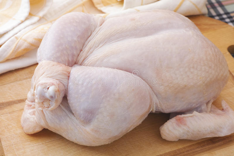 Fresh whole raw chicken on wooden cutting board stock photo