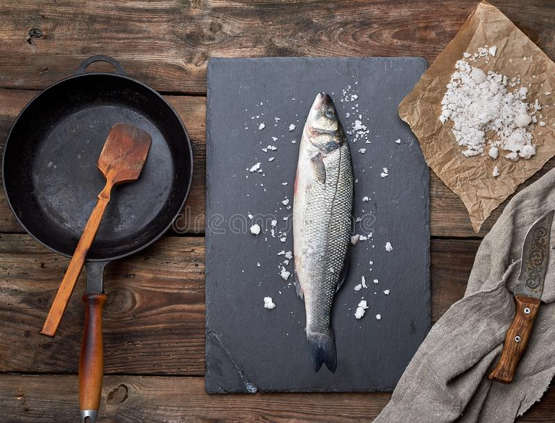 fresh whole sea bass fish on a black graphite board, next to it is an empty round black frying pan stock photography