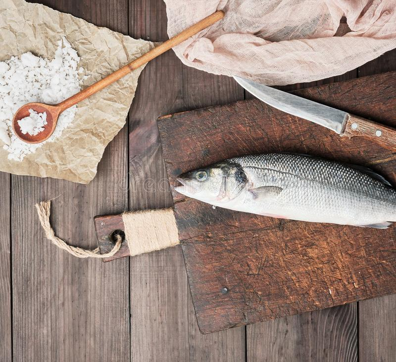 Fresh whole sea bass fish and knife on brown cutting board. Top view stock image