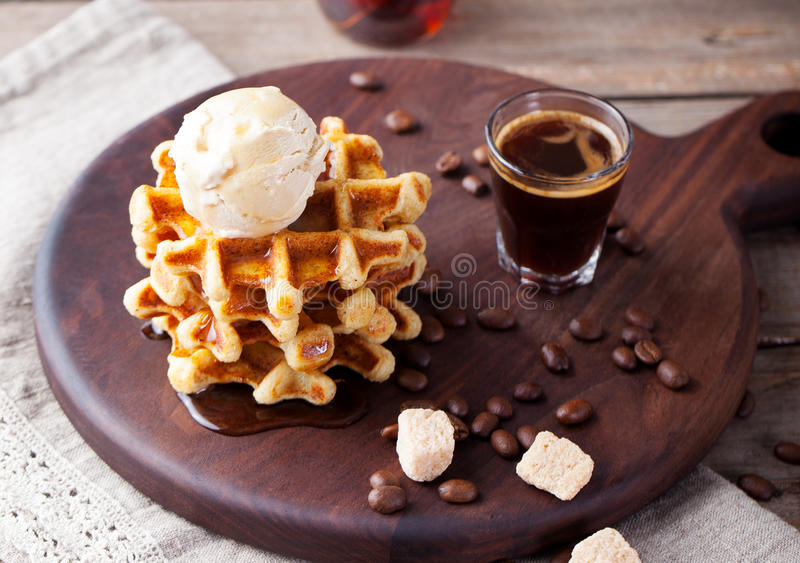 Fresh whole wheat waffles, ice cream, maple syrup royalty free stock photography