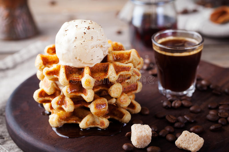 Fresh whole wheat waffles, ice cream, maple syrup. Fresh whole wheat waffles with ice cream, maple syrup and coffee on a wooden background stock photos