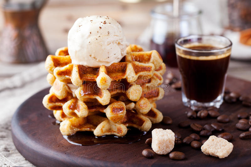 Fresh whole wheat waffles, ice cream, maple syrup. Fresh whole wheat waffles with ice cream, maple syrup and coffee on a wooden background stock images