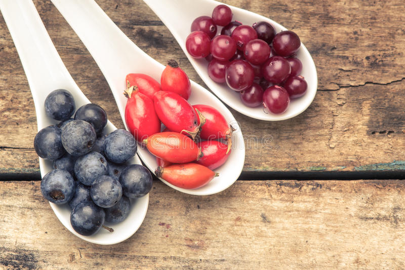 Fresh wild berries in ceramic spoons on wood background. Healthy food stock photo