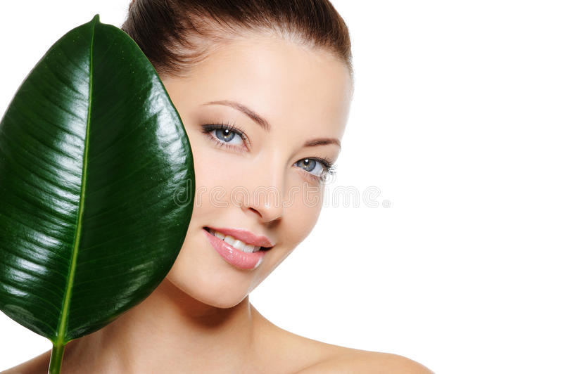 Fresh woman's face with smile and green leaf. Fresh woman's face with cheerful smile and large green leaf over white backgrouns stock photos