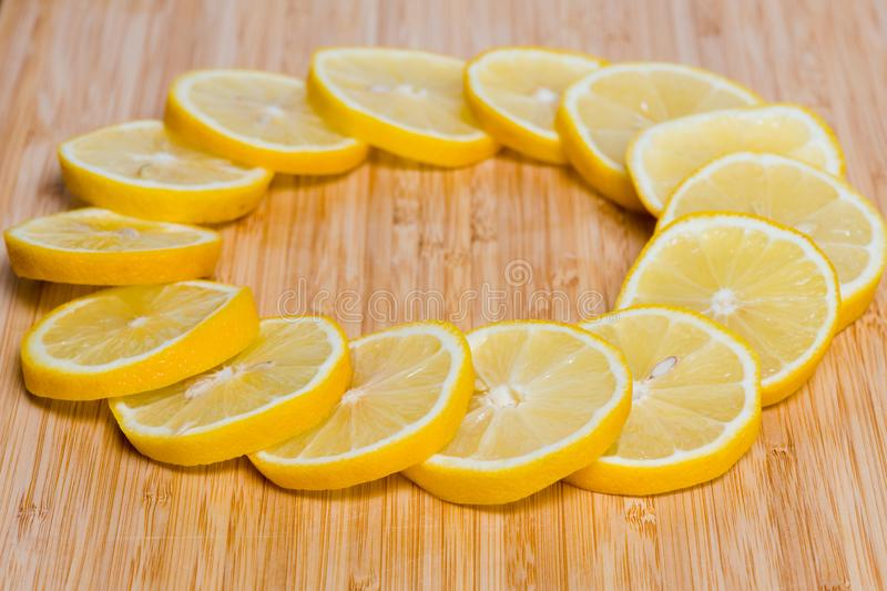 Fresh yellow lemons slices on a wooden background.. sweet lime, vitamin c. Lemon slice. Fresh yellow lemons on a wooden background.. sweet lime, vitamin c stock images