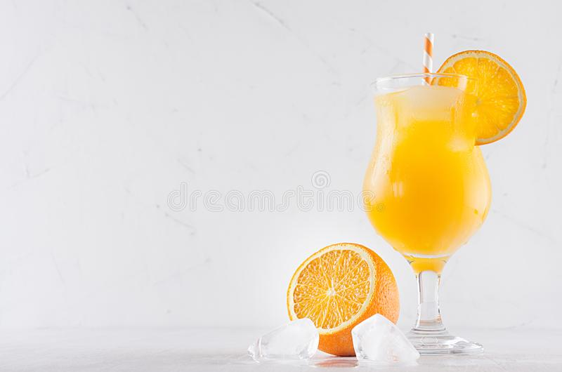 Fresh yellow oranges cocktail in elegance wineglass with ice cubes, straw and half oranges on soft white wood background. stock photography
