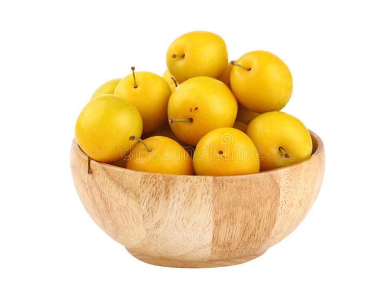 Fresh yellow plums in wooden bowl over white stock photography