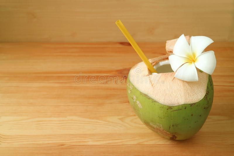 Fresh young coconut water in coconut shell with Plumeria flower on wooden table royalty free stock image