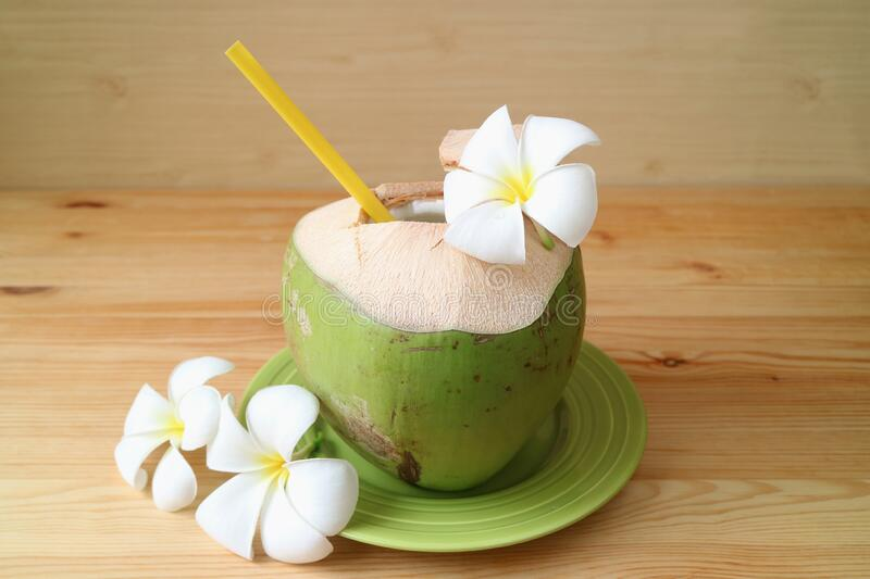 Fresh young coconut with yellow straw and Plumeria flowers ready for drinking. Relaxing time stock image