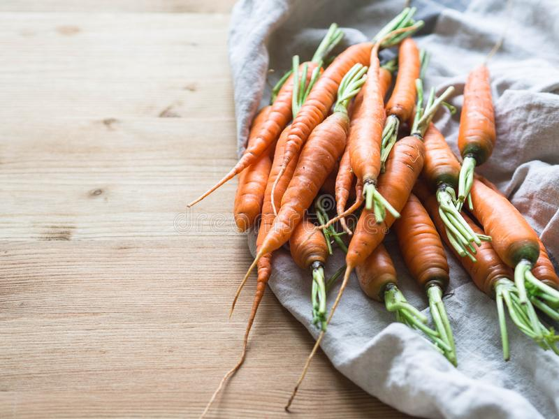 Fresh young orange carrots on a kitchen towel on a wooden table. Copy space royalty free stock photo