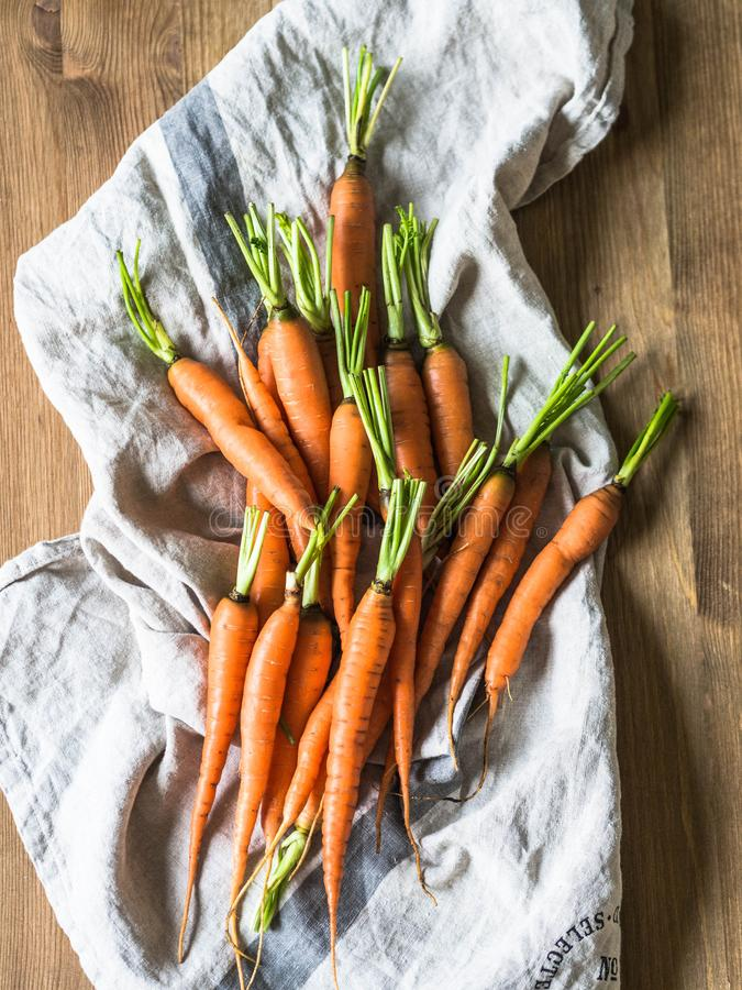 Fresh young orange carrots on a kitchen towel on a wooden table. Copy space royalty free stock photography
