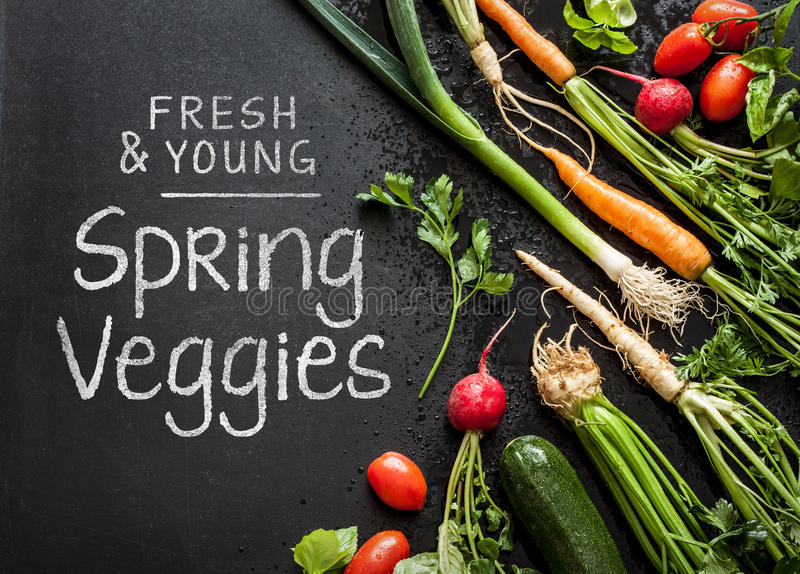 'Fresh and young spring veggies' poster design. Vegetables on black chalkboard from above. Carrots, tomatoes, zucchini, leek, radish, celeriac, parsley and stock photo