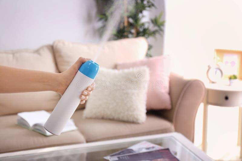 Freshener воздуха женщины распыляя дома стоковые изображения rf