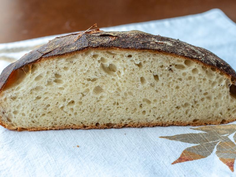 Freshly baked artisan loaf of bread cut to show crumb texture and crusty exterior, resting on a fall themed placemat. On a wodden table stock photo