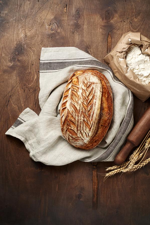 Freshly baked Artisan sourdough bread loaves with wheat spike and bag of flour on dark wooden background. Top view with copy space stock images