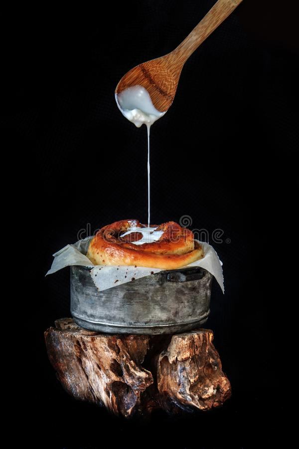 Freshly baked big cinnamon bun with icing dropping from a spoon in a pan with poppy and cocoa filling on parchment paper. Sweet. Freshly baked big cinnamon bun royalty free stock photo