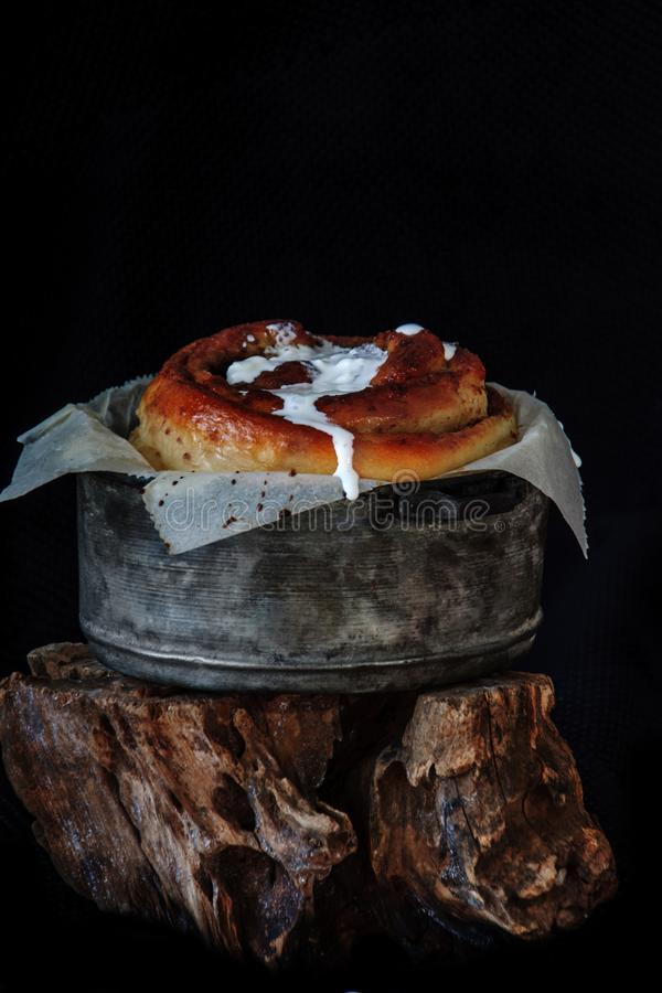 Freshly baked big cinnamon bun with icing in a pan with poppy and cocoa filling on parchment paper. Sweet Homemade Pastry royalty free stock image