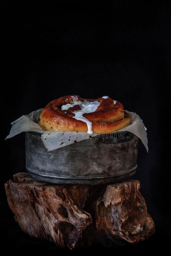 Freshly baked big cinnamon bun with icing in a pan with poppy and cocoa filling on parchment paper. Sweet Homemade Pastry. Christmas baking. - swedish dessert royalty free stock photos