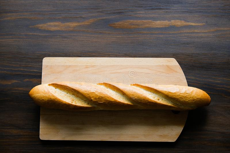Freshly baked bread, kitchen cutting Board on a wooden table, close-up. Copy space for text. The concept of kitchen utensils, royalty free stock photography