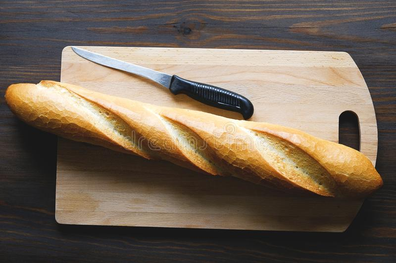 Freshly baked bread, kitchen knife with black plastic handle, cutting Board on a wooden table, close-up. Copy space for text. The stock image