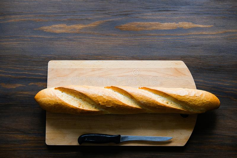 Freshly baked bread, kitchen knife with black plastic handle, cutting Board on a wooden table, close-up. Copy space for text. The stock photo