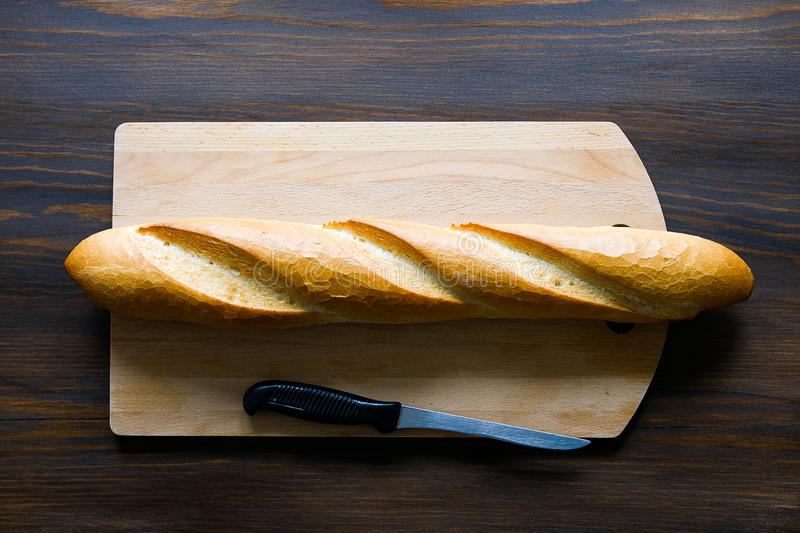 Freshly baked bread, kitchen knife with black plastic handle, cutting Board on a wooden table, close-up. Copy space for text. The royalty free stock photography