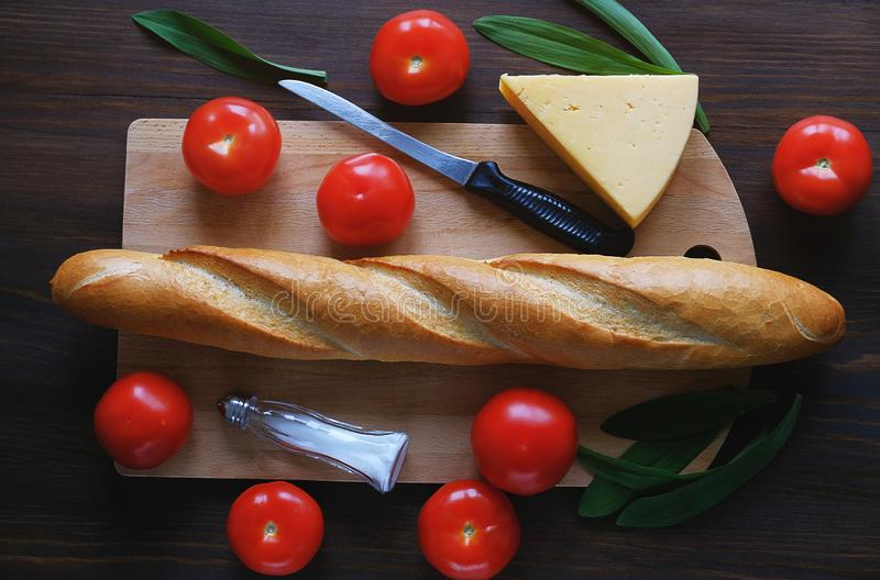 Freshly baked bread, kitchen knife, cutting Board, red tomatoes, salt shaker, cheese, greens on a wooden table, close-up. The stock image