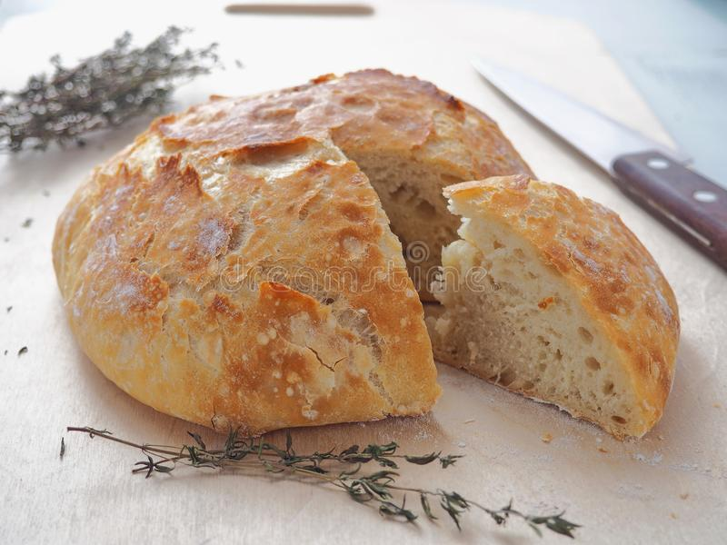Freshly baked bread with thyme sprig upon cutting board. One piece is cut. stock photography