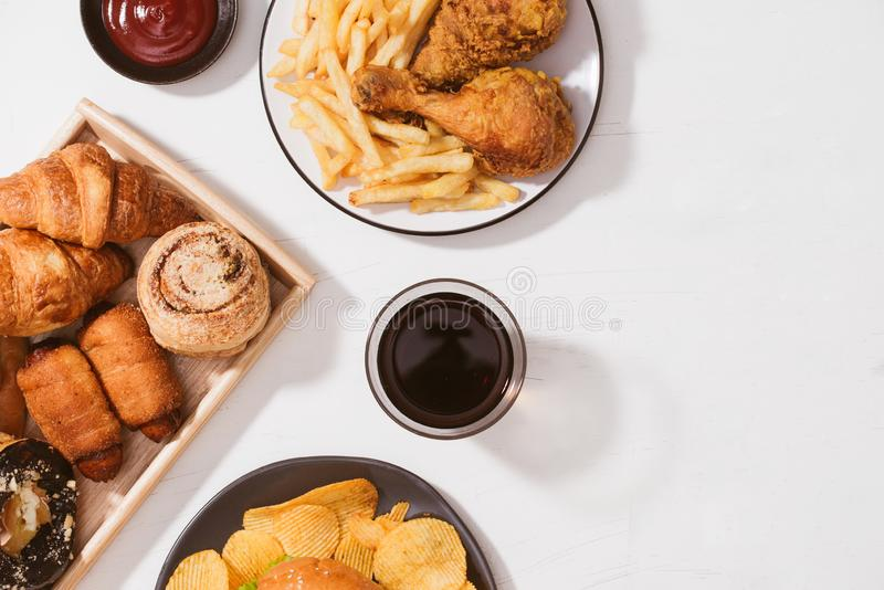 Freshly baked buns, big hamburger, fried crispy chicken and french fries on white table - Unhealthy food concept.  royalty free stock photography