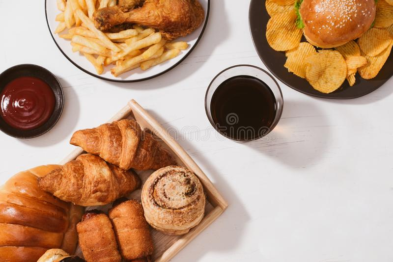 Freshly baked buns, big hamburger, fried crispy chicken and french fries on white table - Unhealthy food concept.  stock photo