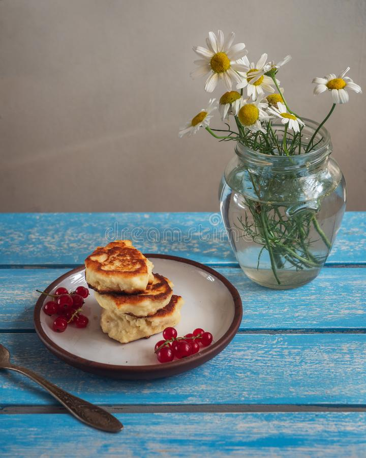 Freshly baked cheesecakes with currants on a wooden tray. A small bouquet of flowers stock photos
