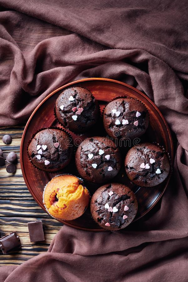 Freshly baked chocolate muffins sprinkled with candy hearts on an earthenware plates stock photo