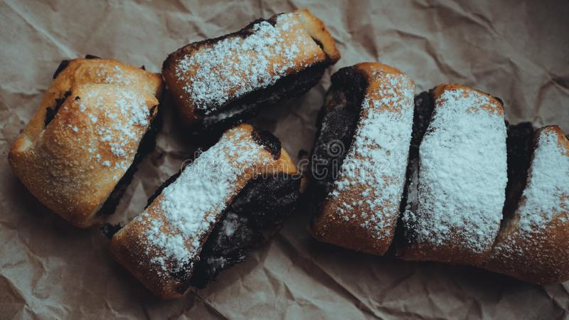 Chocolate Rolls sprinkled with powdered sugar. Background of craft paper. Freshly Baked Chocolate Rolls with a delicious filling, sprinkled with powdered sugar stock photo