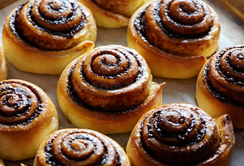 Freshly baked cinnamon buns with cacao and spices. Close-up. Sweet christmas baking. Kanelbulle - swedish dessert. stock image