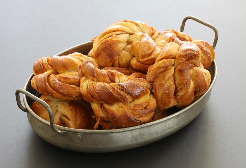 Freshly baked cinnamon buns. Cinnamon roll pastries in a pile in an antique metal tray close up. Stock photo stock photo