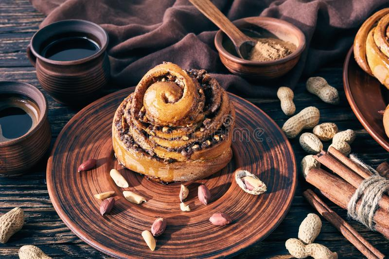 Freshly baked Cinnamon rolls bun, close up. Freshly baked Cinnamon rolls buns with peanuts served on a earthenware plate and two cups of coffe on an old wooden royalty free stock photography