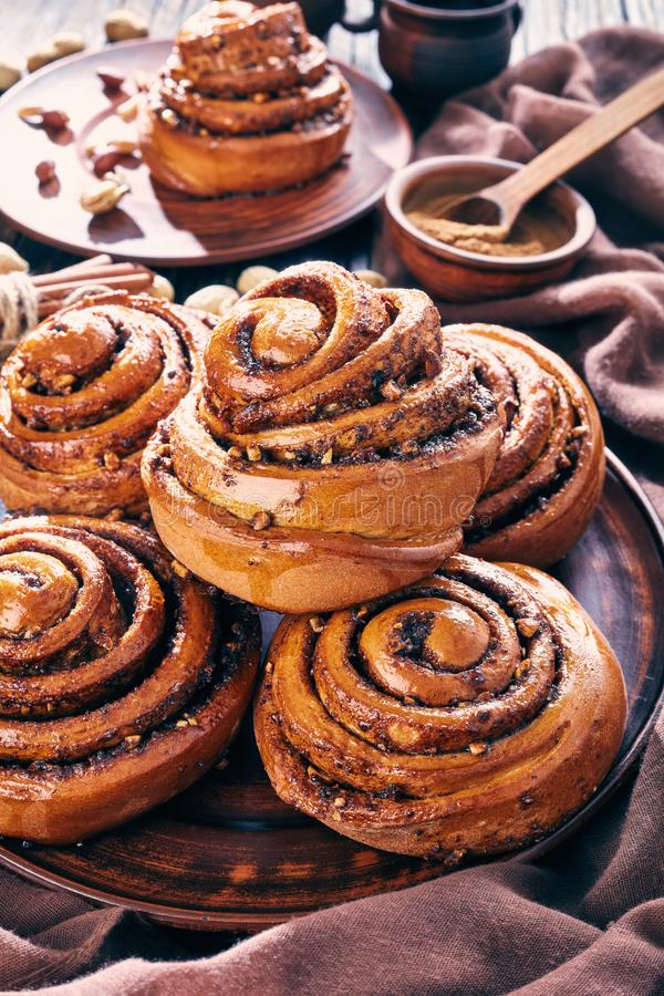 Freshly baked Cinnamon rolls bun, close up. Freshly baked Cinnamon rolls buns with peanuts served on a earthenware plate and two cups of coffee on an old wooden stock images