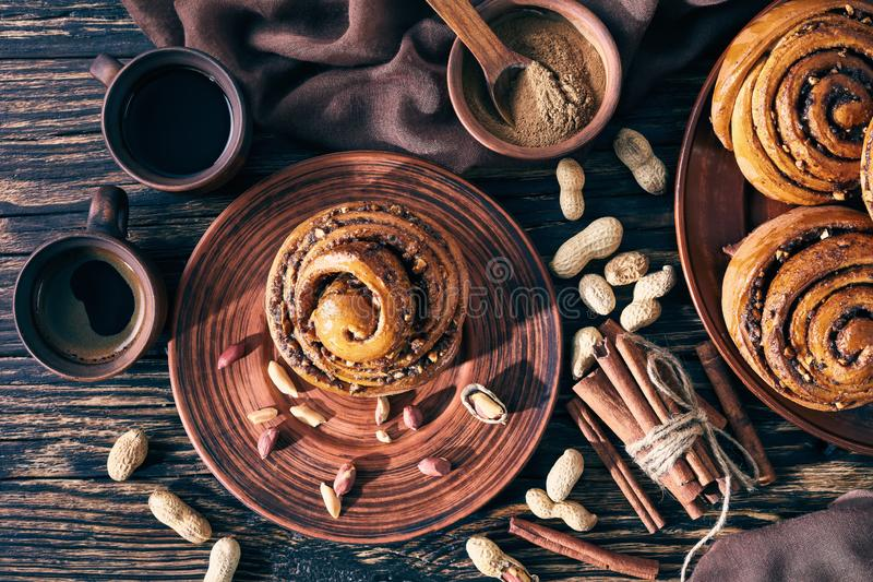 Freshly baked Cinnamon rolls buns, top view. Freshly baked Cinnamon rolls buns with peanuts on a earthenware plate with brown cloth, two cups of coffee and stock photography