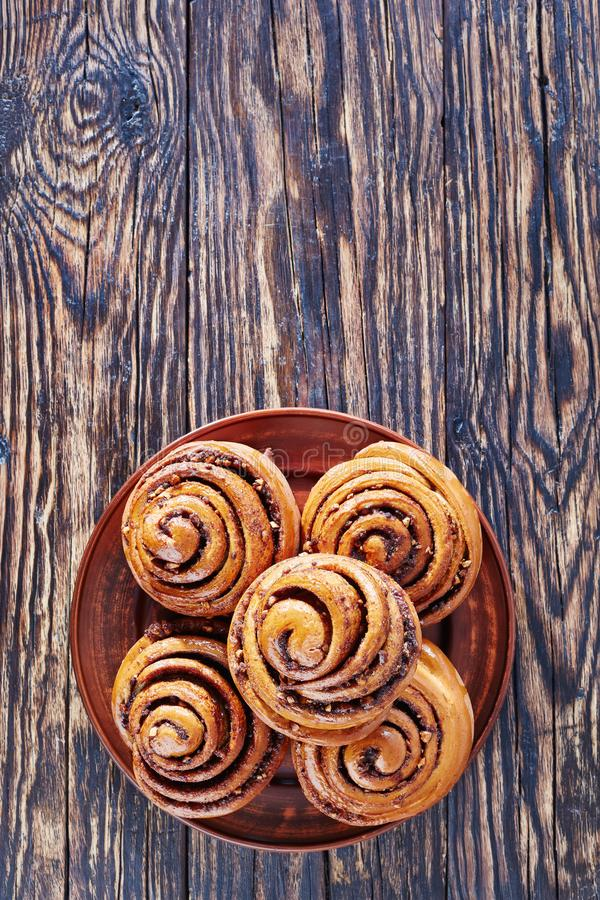 Freshly baked Cinnamon rolls buns, top view. Freshly baked Cinnamon rolls buns with peanuts served on a earthenware plate. Kanelbulle swedish dessert, vertical royalty free stock photography