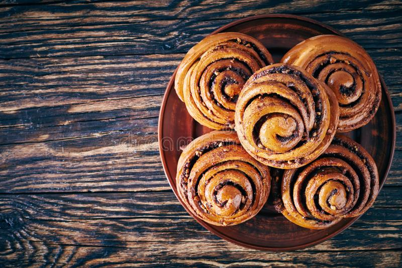 Freshly baked Cinnamon rolls buns, top view. Freshly baked Cinnamon rolls buns with peanuts served on a earthenware plate. Kanelbulle swedish dessert, view from stock photos