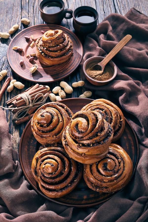 Freshly baked Cinnamon rolls buns, top view. Freshly baked Cinnamon rolls buns with peanuts served on a earthenware plate and two cups of coffee on an old wooden royalty free stock photos