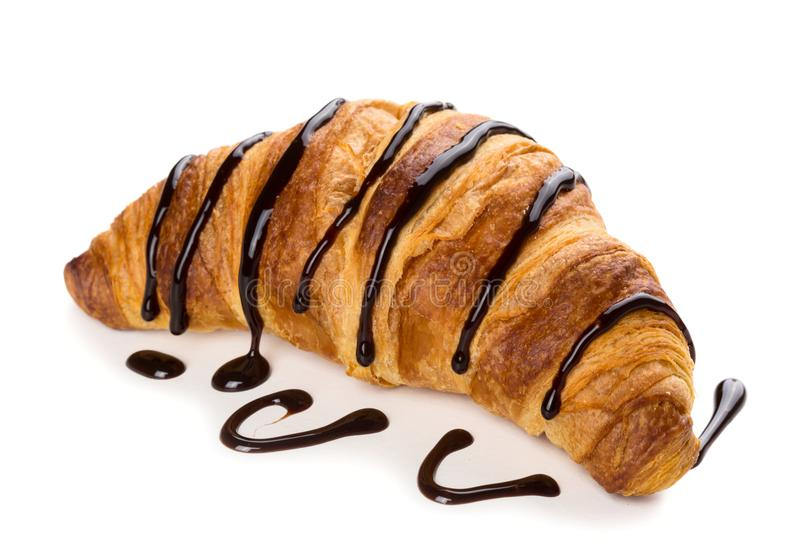 Croissant with chocolate sauce. Freshly baked croissant decorated with chocolate sauce stock photo